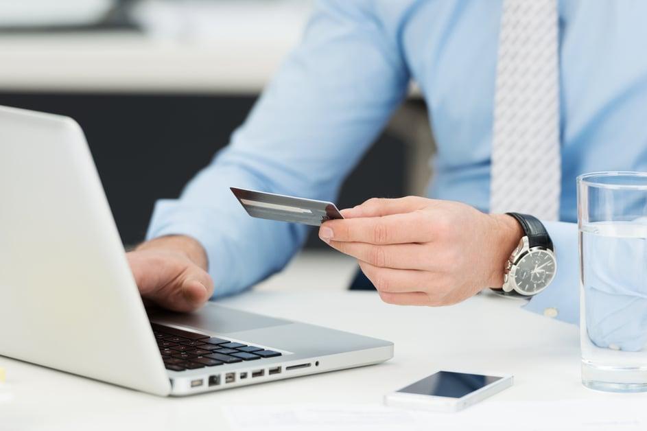 Hombre de negocios hace operaciones bancarias en línea, hace un pago o compra bienes en Internet, ingresa los detalles de su tarjeta de crédito en una computadora portátil, vista de cerca de sus manos