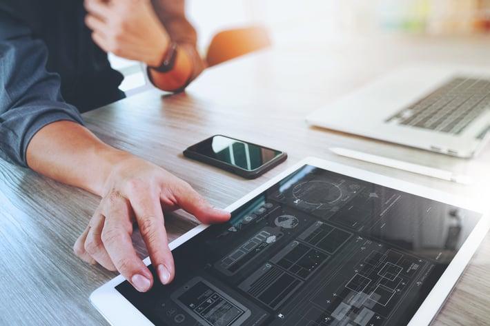 Diseñador de sitios web trabajando en tableta digital y computadora portátil con un teléfono inteligente y un diagrama de diseño de gráficos en el escritorio de madera como concepto